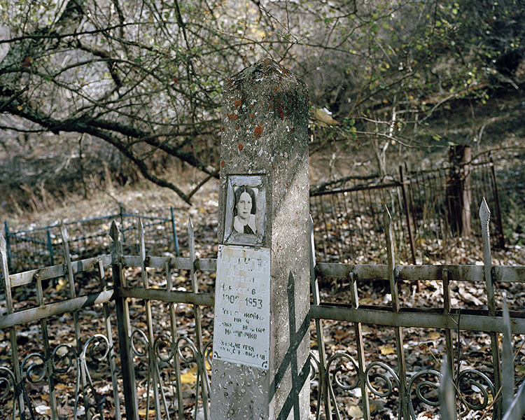 A Soviet grave with a picture of a woman. An old and forgotten cemetery is situated on the other side of the Kattasay stream than the city. Most of the inhabitants of Yangiabad and workers of the mines were people from Russia.